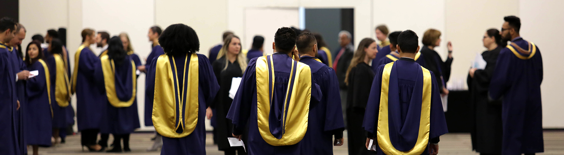 Students in graducation robes walking towards an open door